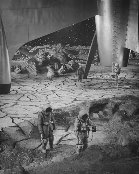 Actors in space suits outside rocket ship while midget actors in space suits work in bkgrd. because their smaller size gives illusion of distance