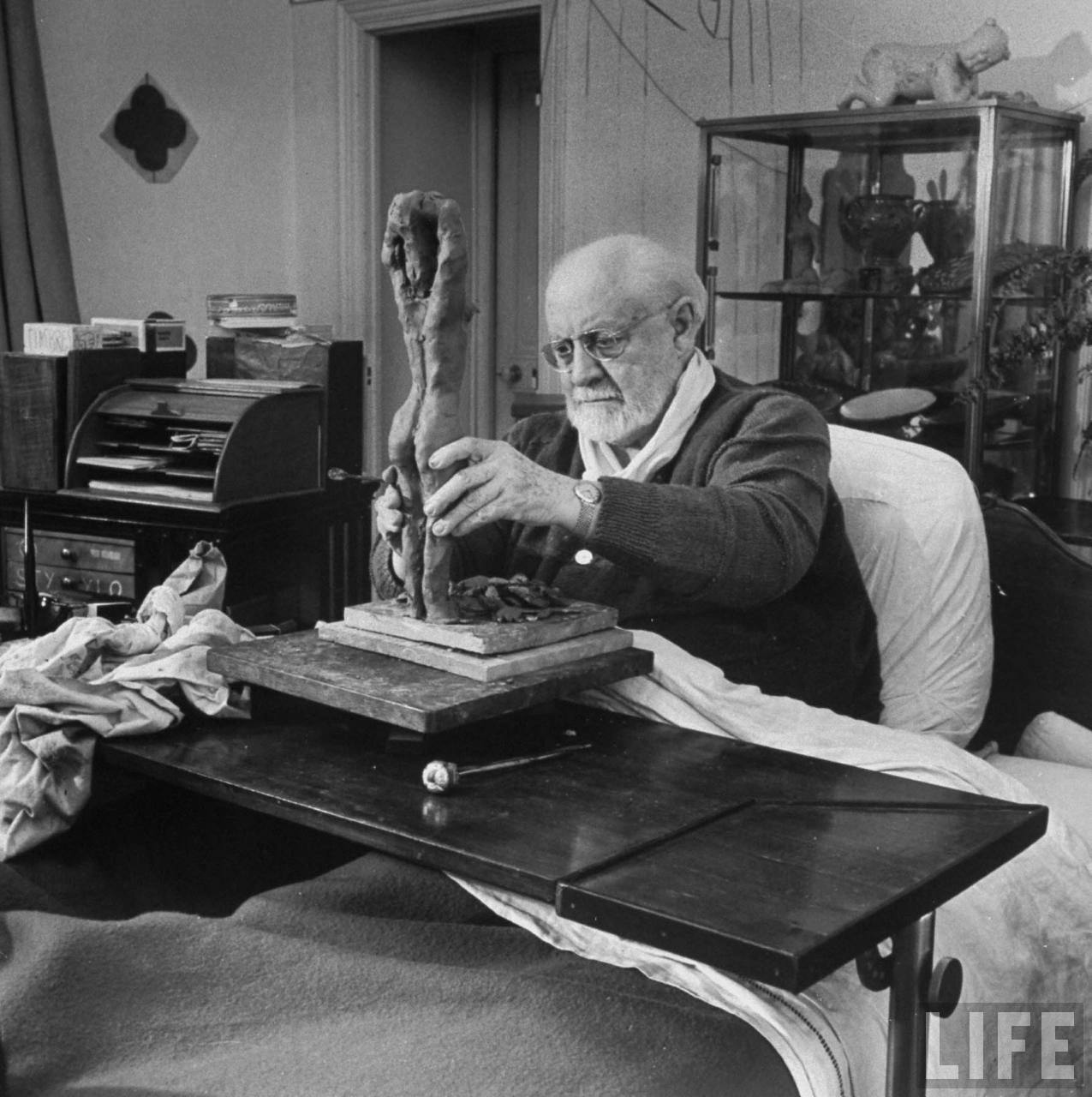Henri Matisse sculpting nude female figure while sitting in bed in his apartment, France, by Dmitri Kessel, 1951. Google LIFE Archive