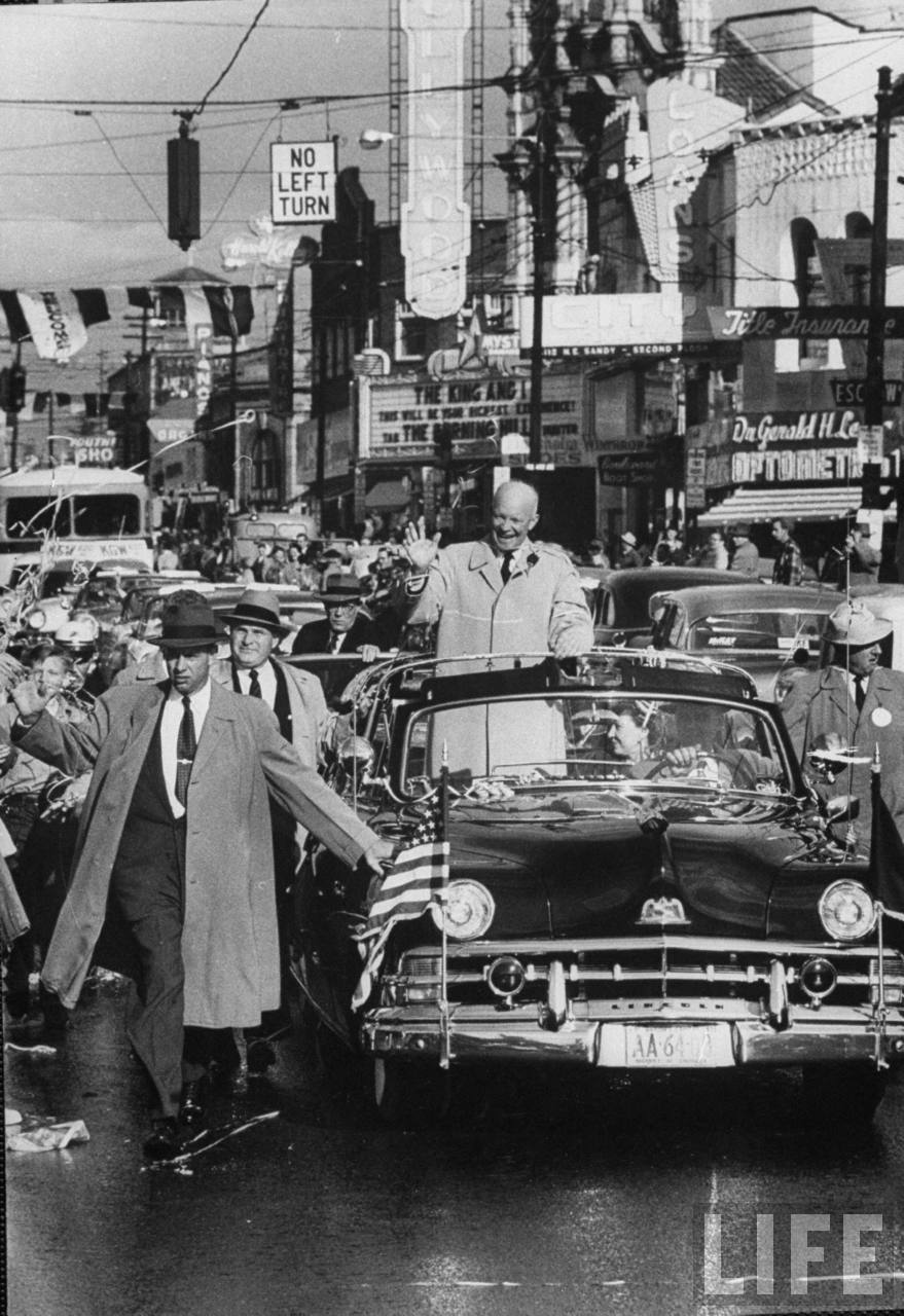 Dwight D. Eisenhower and his wife campaining, driving in car, waving to crowds.