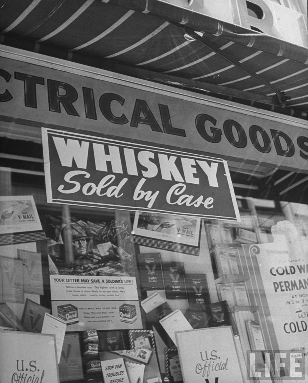 Sign on liquor store encouraging customers to buy quantity in Kansas City, MO. August 1945