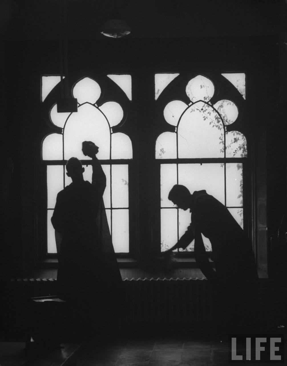 Monks cleaning windows of the monastery's sacristy, two young clerics exemplify St. Benedict's ruling that all be employed in the work, and that then are the monks in truth if they live by the work of their hands.