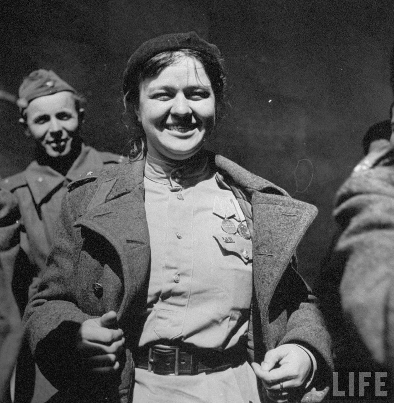 Female Russian soldier grinning broadly while showing off her medals and a US Army Officers insignia pinned to her shirt after the Allied troops met following the fall of Berlin.
