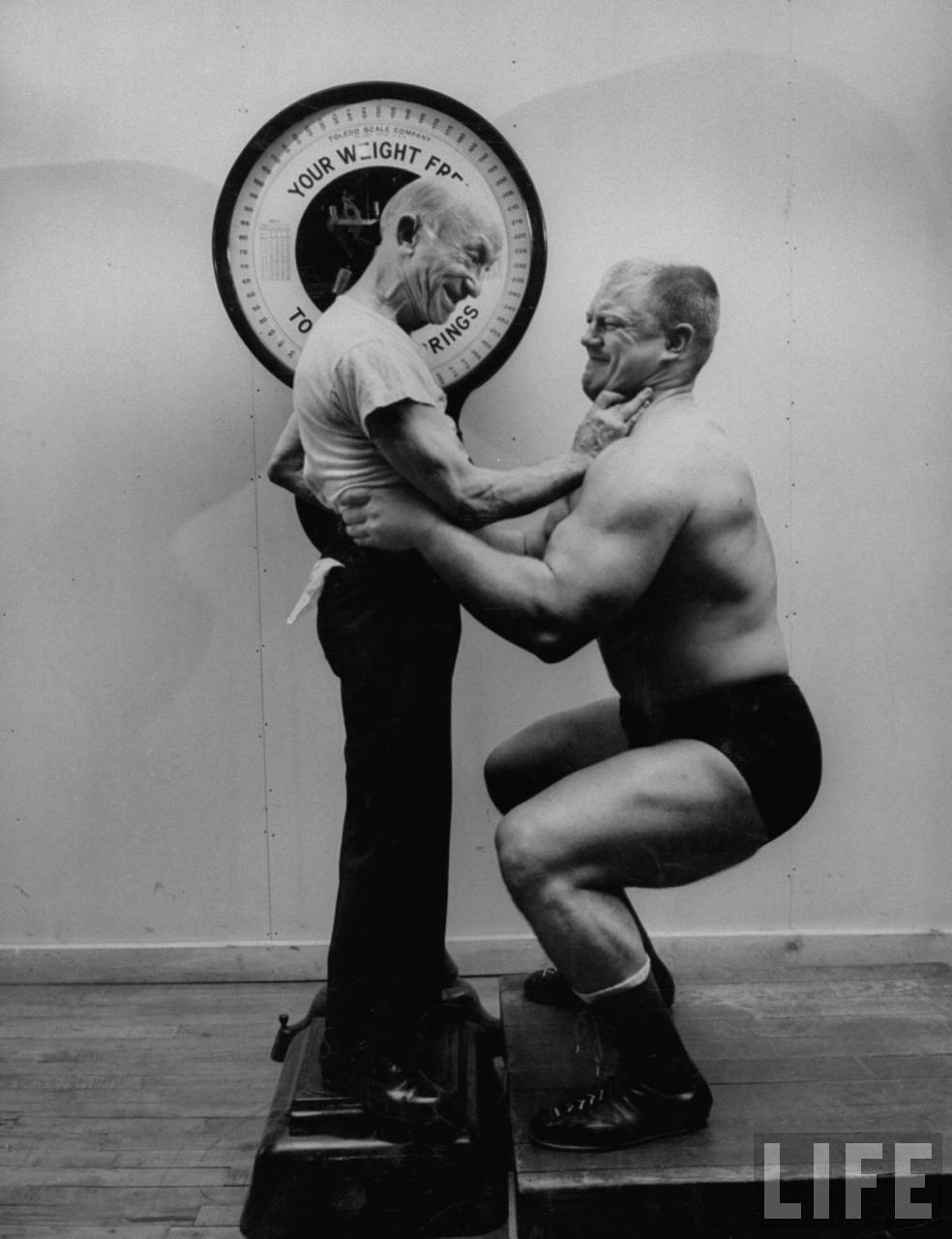 Westler Dick Afflis (R) failing in attempt to lift Johnny Coulon, the unliftable man, from scale.