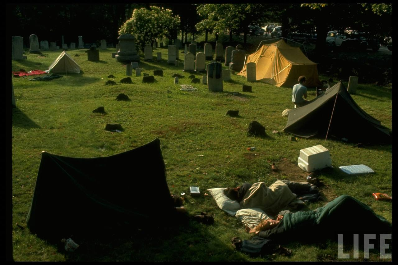Young people camping out w. tents in the midst of a cemetery, during the Woodstock Music & Art Fair.