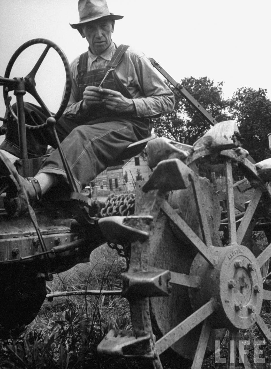 Farmer sitting on plow.