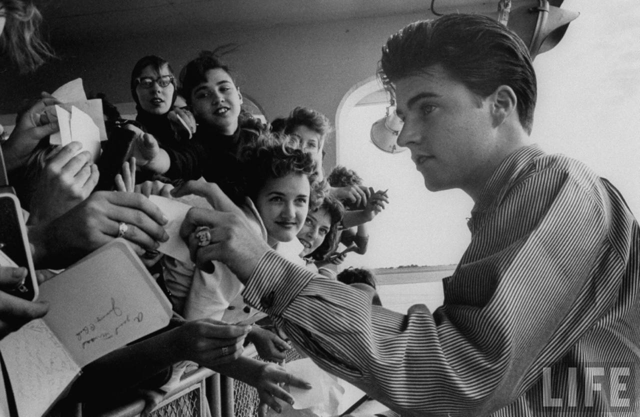 Rock singer/actor Ricky Nelson signing autographs for mob of young female fans pressed against fence at airport upon his arrival for a concert.