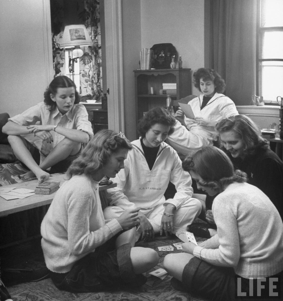 College girls playing cards in their room.
