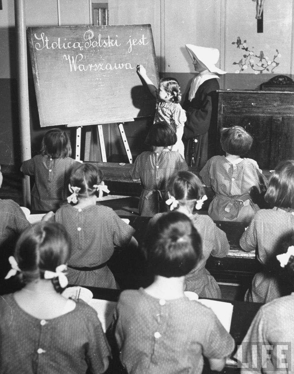A girl working at the chalkboard of a classroom while a nun and her classmates look on.