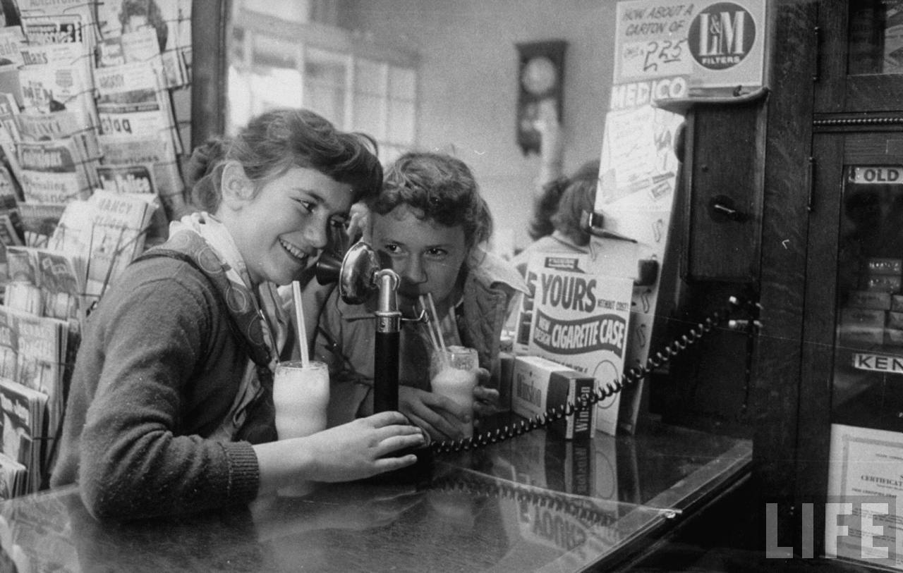 Teenage girls drinking milkshakes at a local restaurant in Lebanon, KS. February 1957
