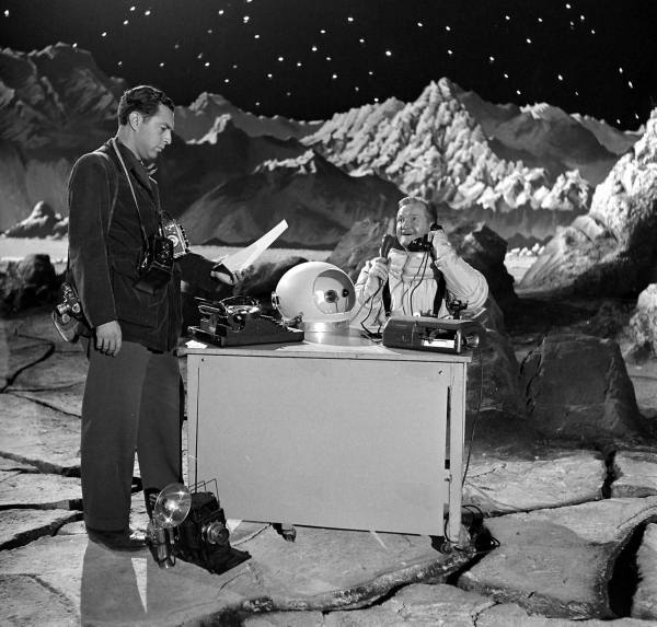 "Man festooned with cameras, and man in space suit talking on telephone, on Destination Moon""s lunar surface set"