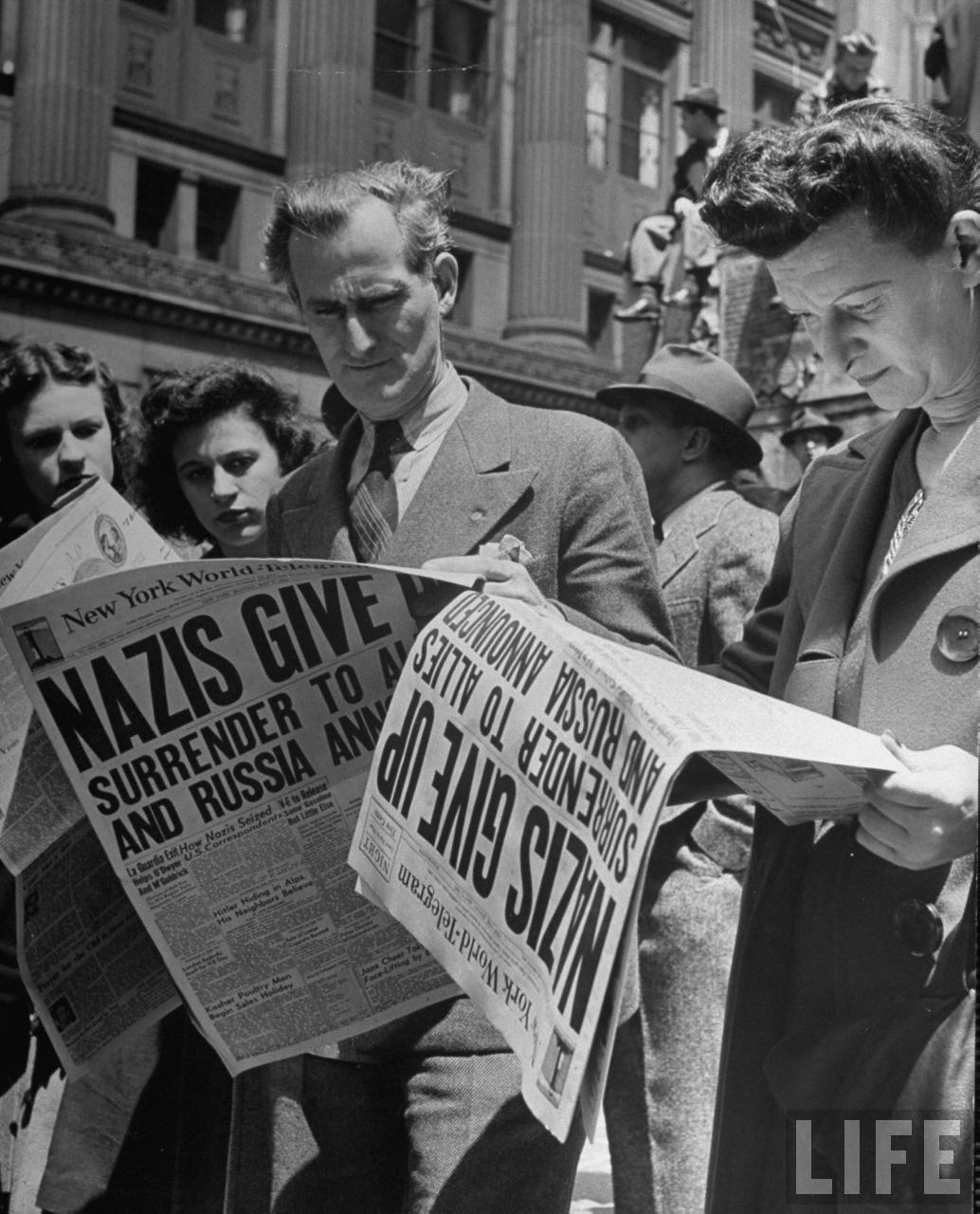People eagerly reading New York World-Telegram newpapers w. the headline NAZIS GIVE UP/SURRENDER TO ALLIES AND RUSSIA ANNOUNCED, at newsstand in Times Square as people gather for massive end to war in Europe celebration.