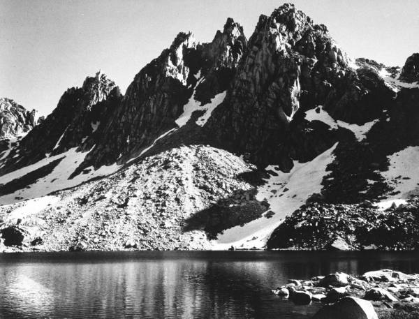 """Kearsarge Pinnacles,"" partially snow-covered rocky formations along the edge of the river."