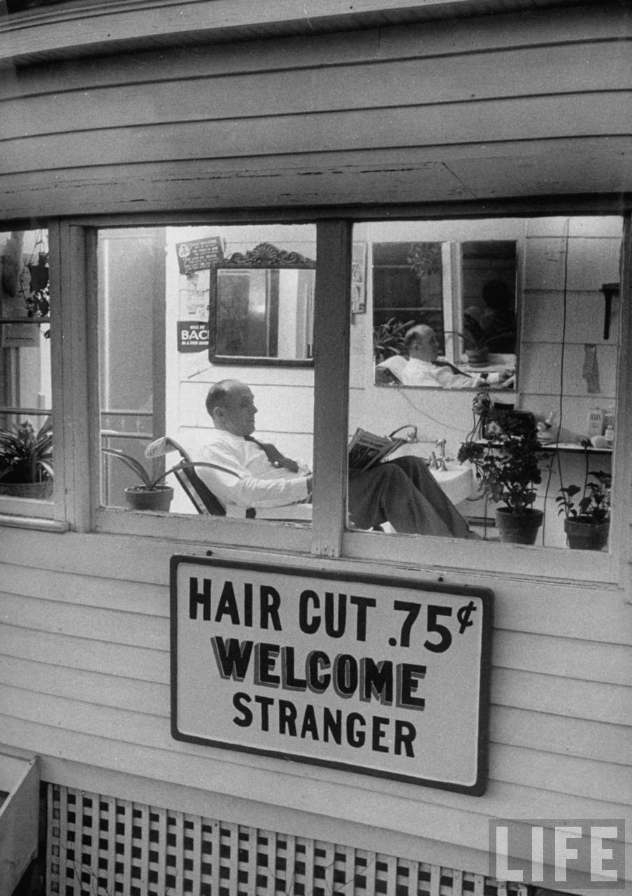 A man waiting in a barber shop for a haircut in Lebanon, KS.	February 1957