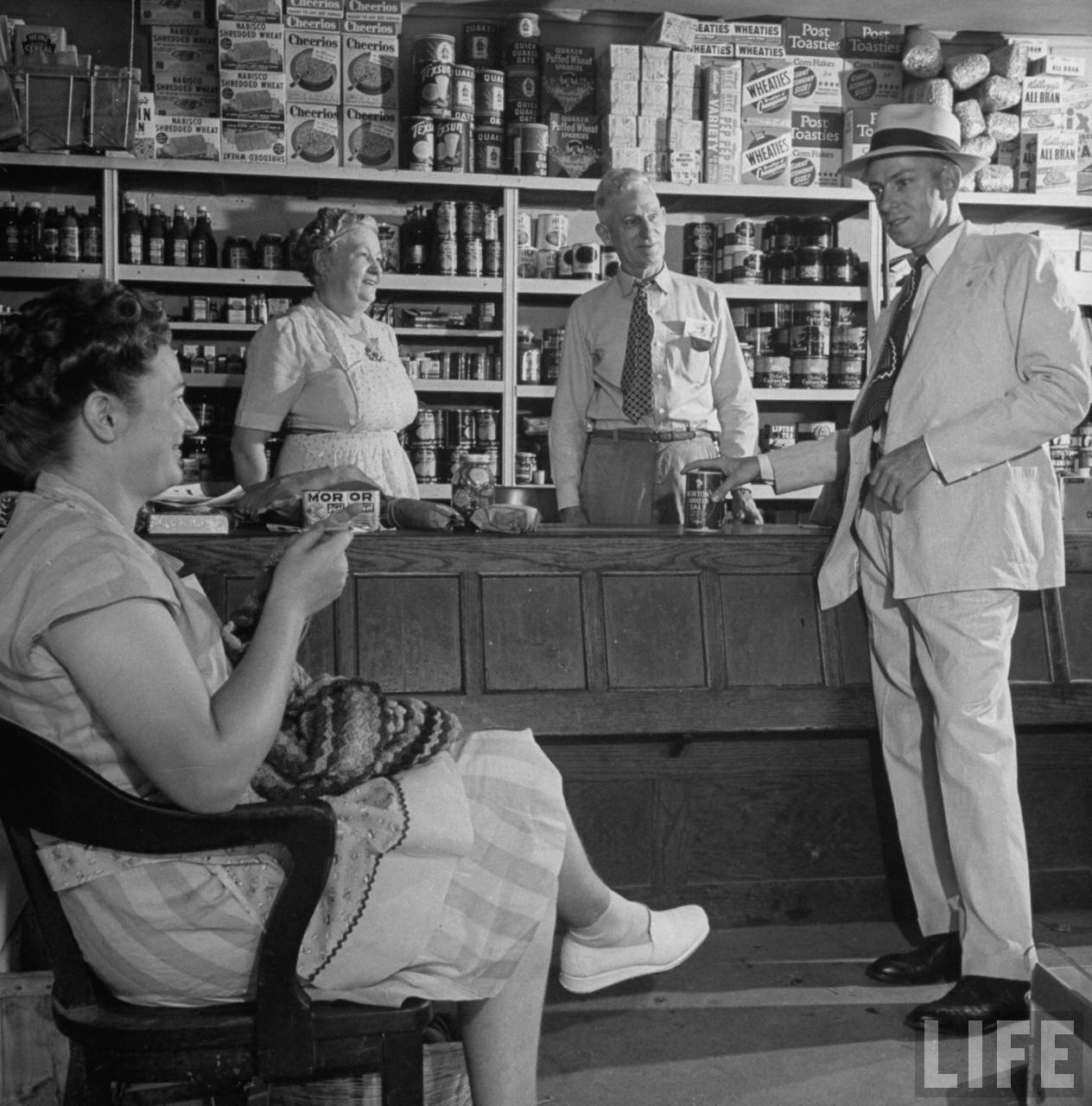 Enos A. Axtell (R), a candidate for office, standing with his family in the grocery store owned by his parents in Kansas City, MO. July 1946