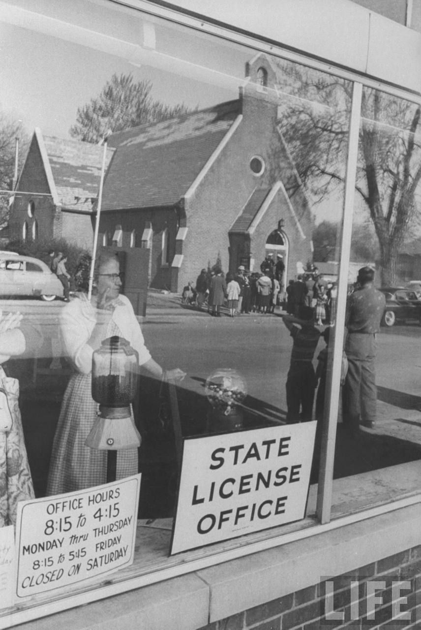 Reflected excitement registers in the window of the License Bureau, two ladies look across Liberty Street to the Trinity Episcopal Church where a group has clustered to catch sight of Margaret Trumans wedding party when it leaves after rehearsing the ceremony, the day before the great event.