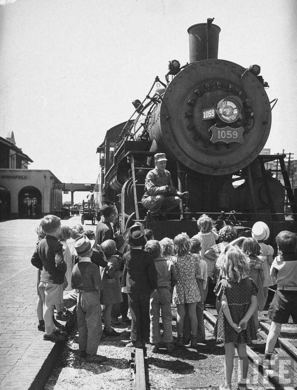 A view of a class learning about trains first hand at a railroad station.