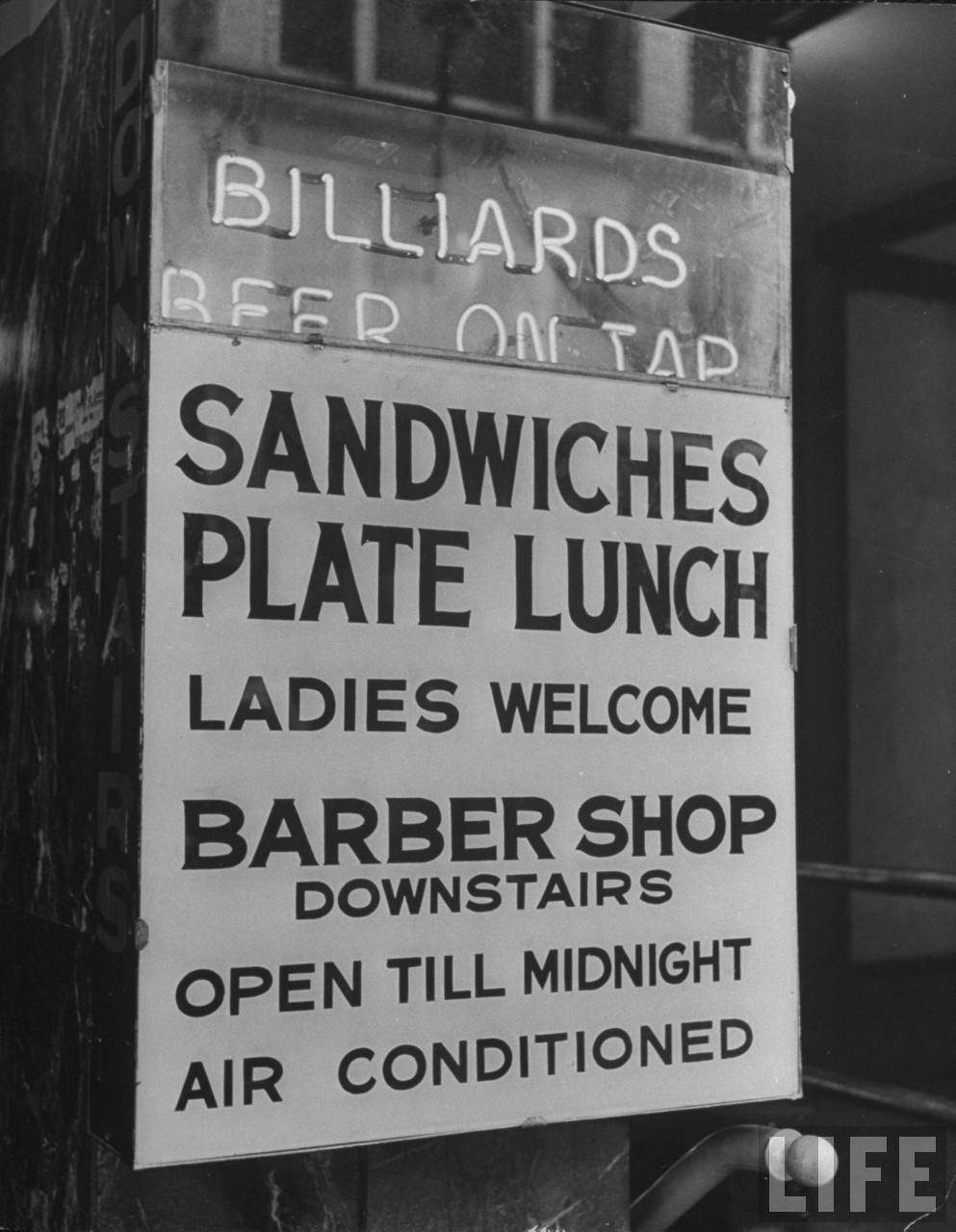 Sign on window advertising a variety of services available in	Kansas City, MO. August 1945