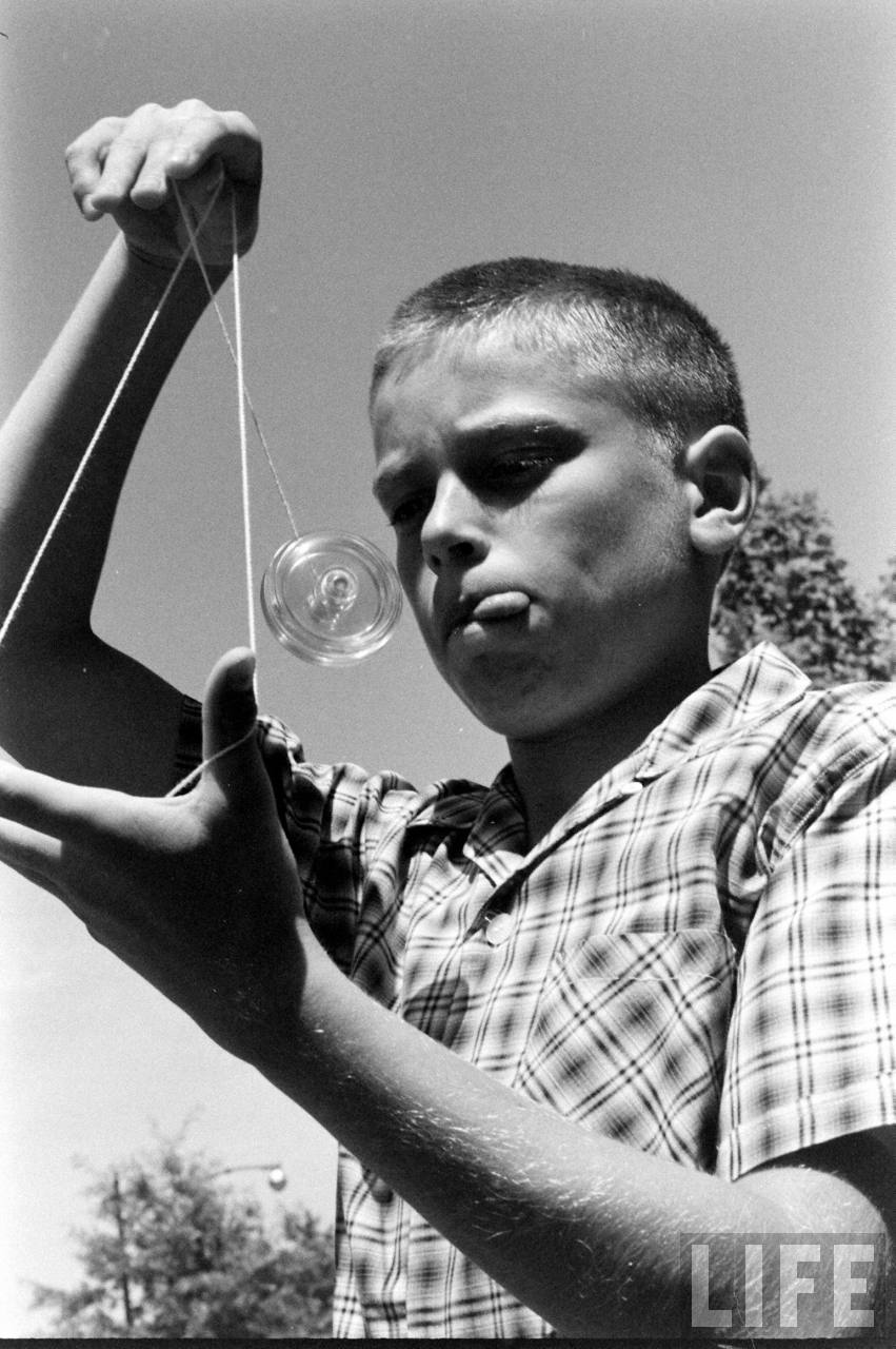 Young boy w. tongue sticking out between pursed lips, concentrating on performing rocking the baby maneuver w. his yo-yo.