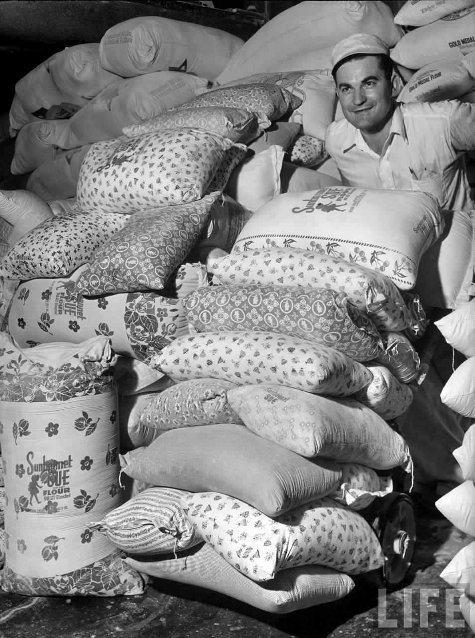 Warehouse worker wheeling colorfully printed flour sacks which housewives use to make dresses because the labels wash out, at Sunbonnet Sue flour mill.
