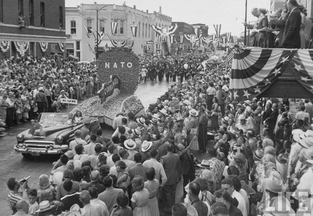 View of Dwight D. Eisenhower parade down Main Street, with Ike and Mamie watching from balcony.
