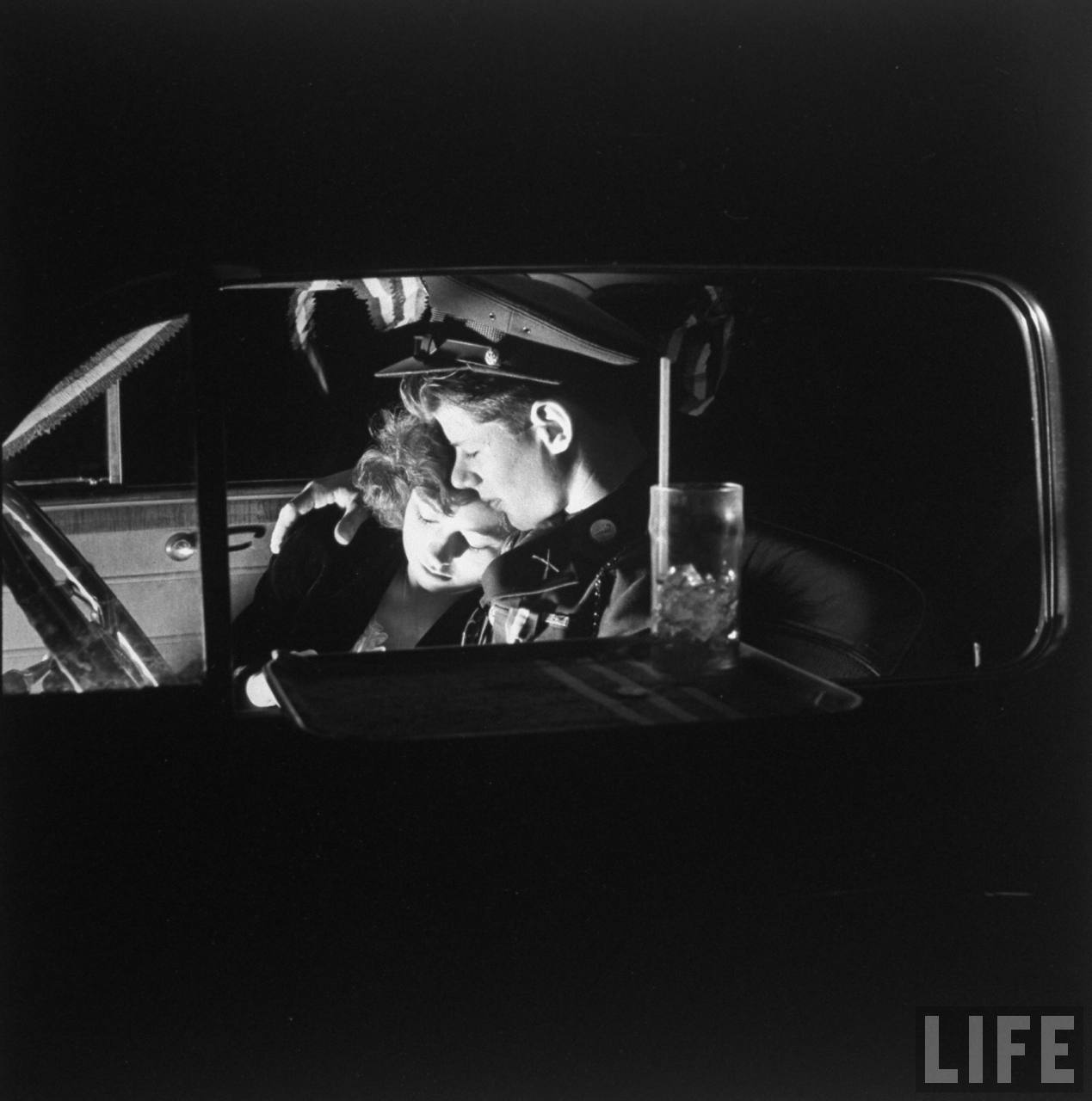ROTC cadet Lieutenant William Ackenhauser snuggling in front seat of car with his date Joanne Warren, with tray attached to the vehicles open window at the Nu-Drive-In restaurant.