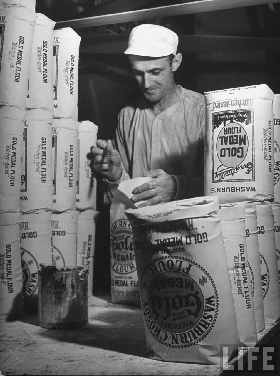 Worker brushing paste on end edges of freshly-filled sacks which he will then put upside down (R) until the paste dries at WASHBURN'S GOLD MEDAL FLOUR mill.