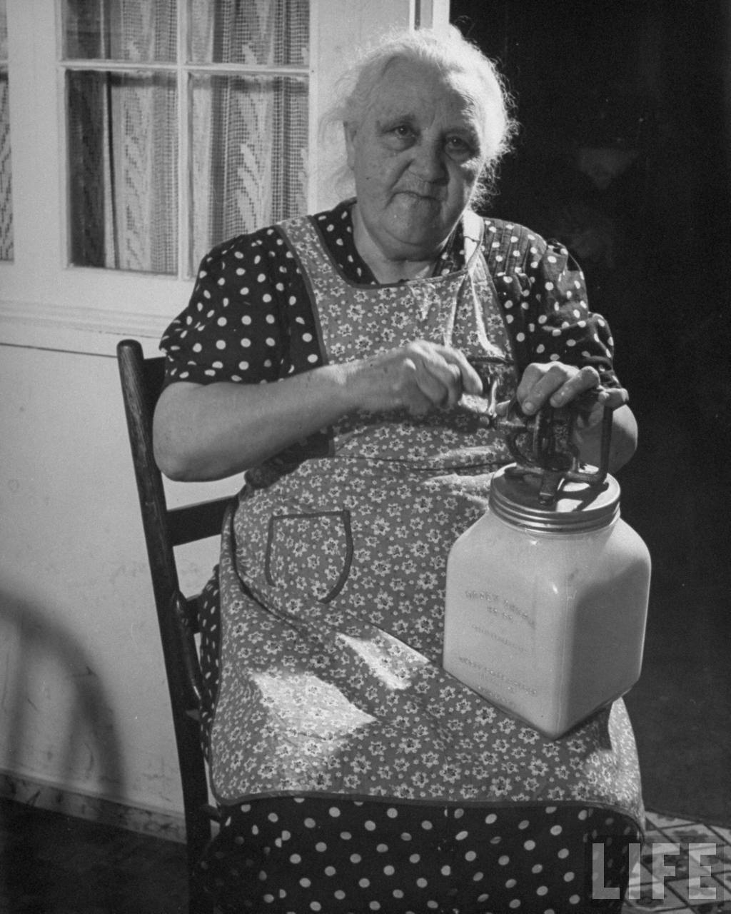 Woman sitting in chair and churning butter.