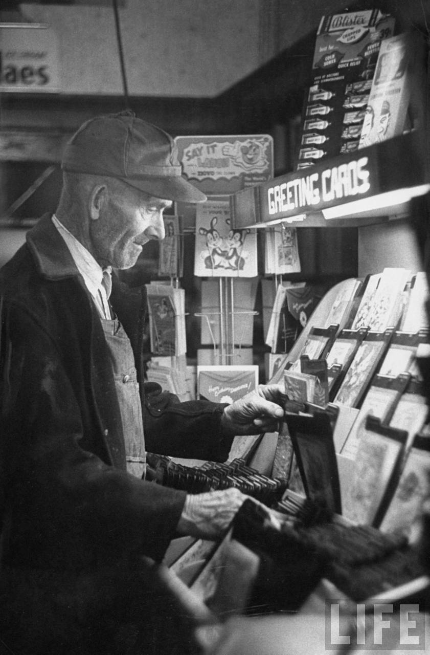 A man buying a greeting card from a drugstore in Lebanon, KS. February 1957