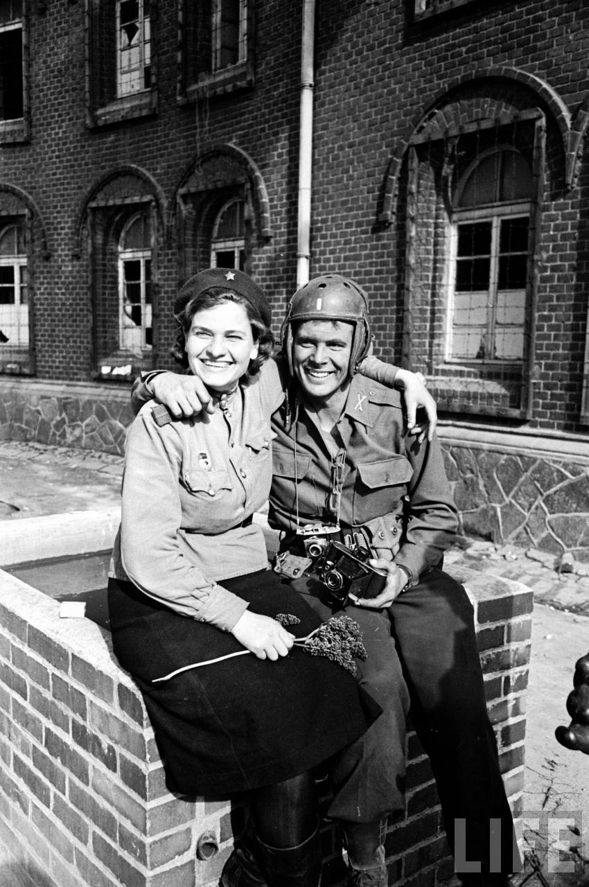 Female Russian soldier and American trooper happily sitting together after meeting near the city of Torgau; by Davis Scherman & John Florea.