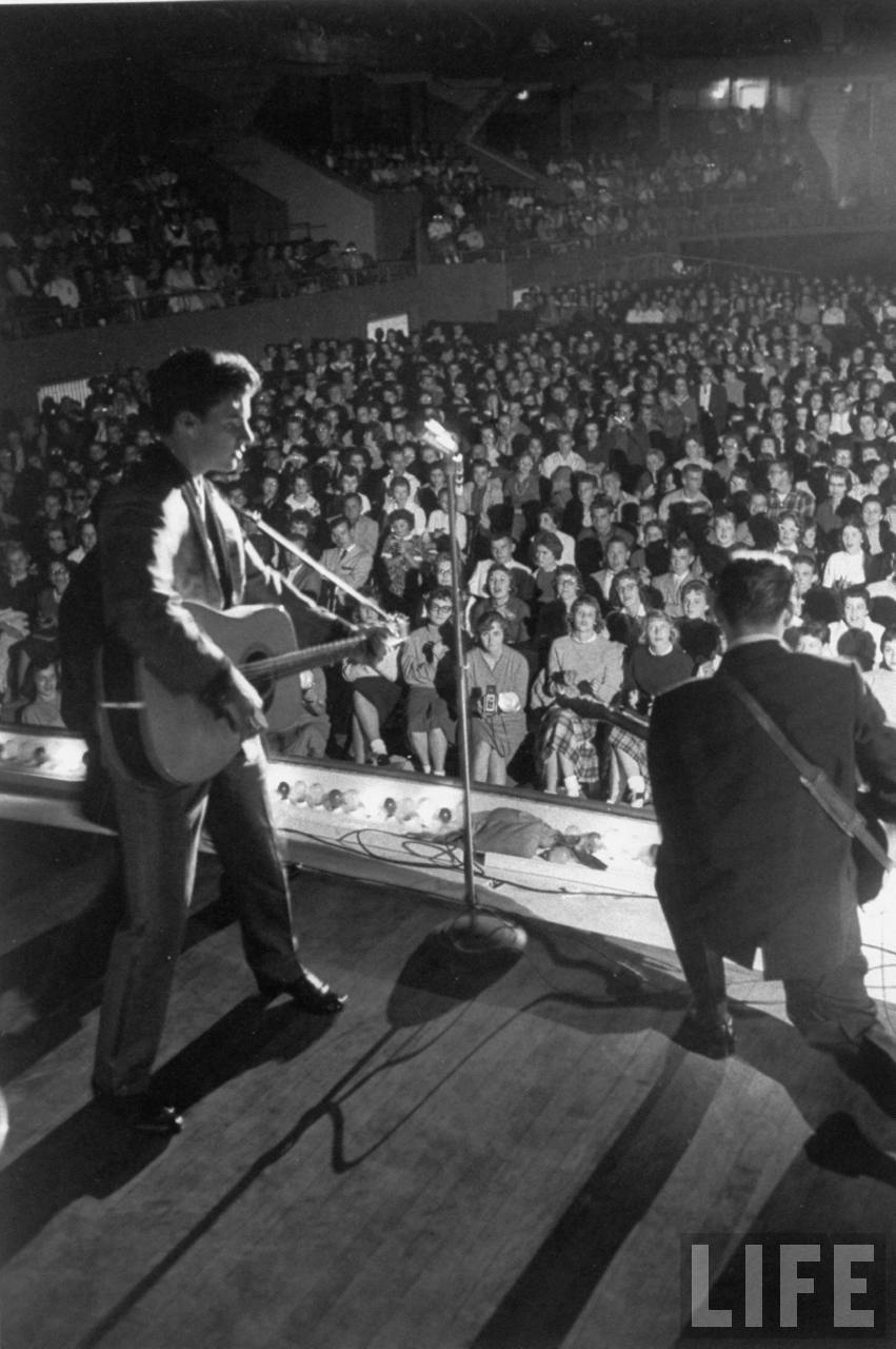 Rock singer/actor Ricky Nelson (L) singing & playing guitar w. his lead guitarist James Burton on stage overlooking 5,000 rapt young fans during concert.