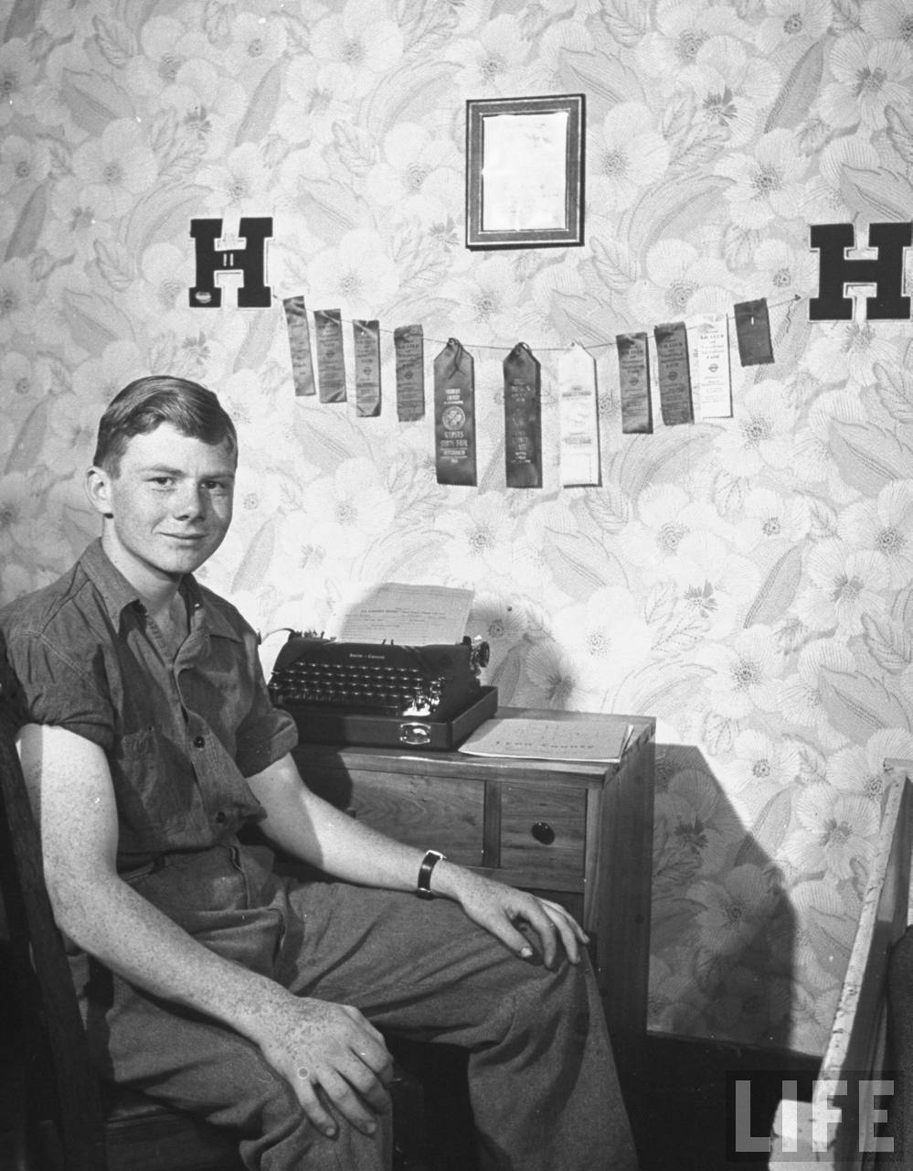 Kansas Farm Boy, Dan Gardner in his room seated at his desk with 4-H club ribbons awarded to him on his many projects.